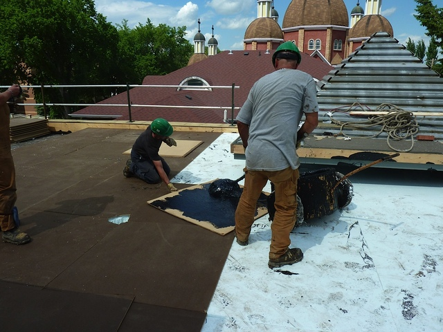 June 22, 2011 - Preparing the roof - tar is applied to backside of panel that is put over the styrofoam